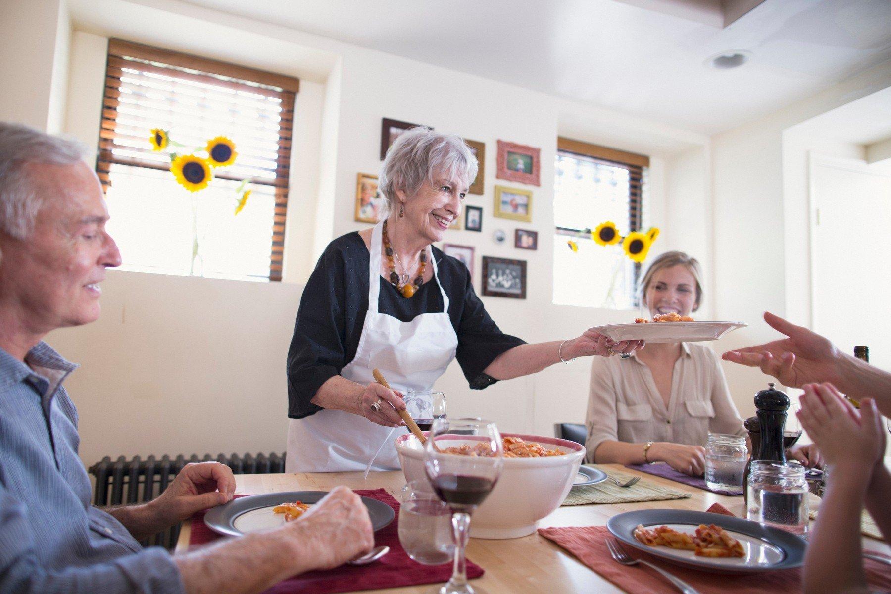 Žena servíruje rodinnou večeři