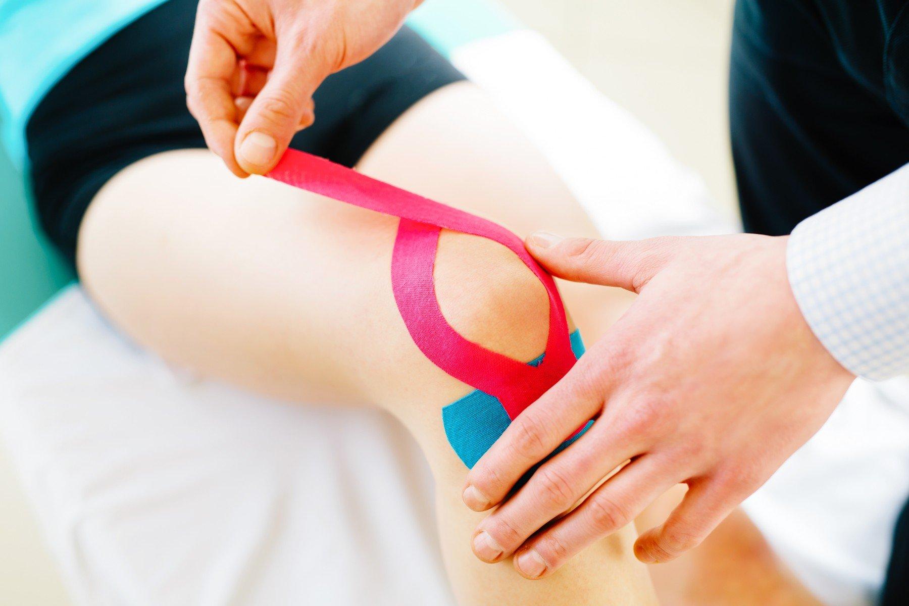 Fyzioterapeut aplikuje ženě na koleno kinesiotape