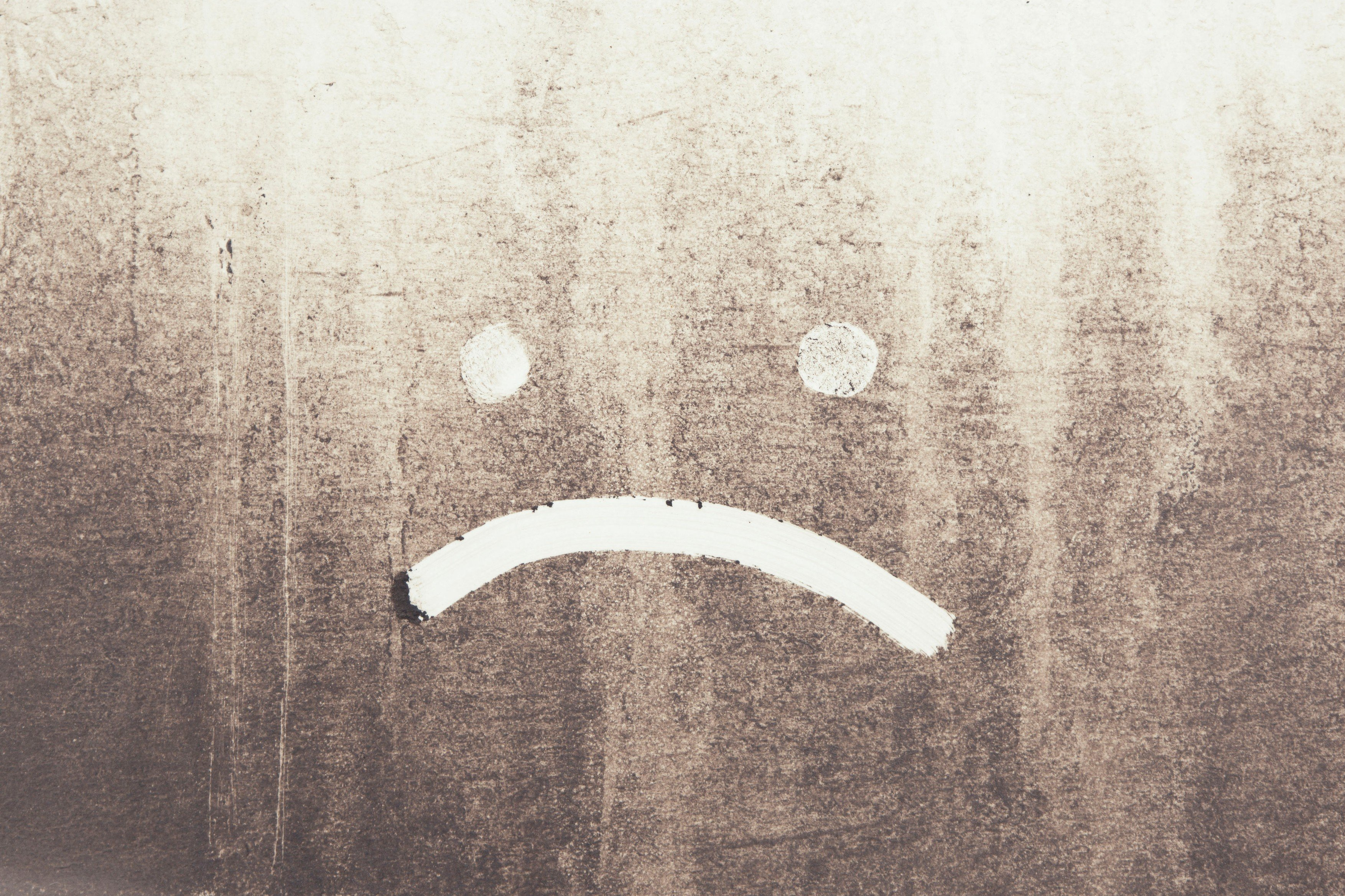 Prach, špína, smutný smajlík, deprese. Ilustrační foto