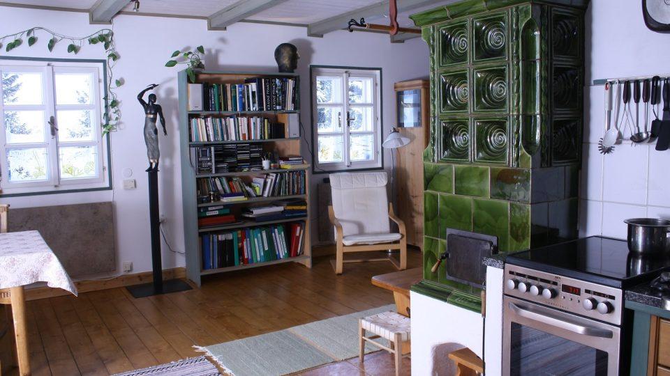 Krásná kachlová kamna jsou dominantou obývacího prostoru propojeného s kuchyní