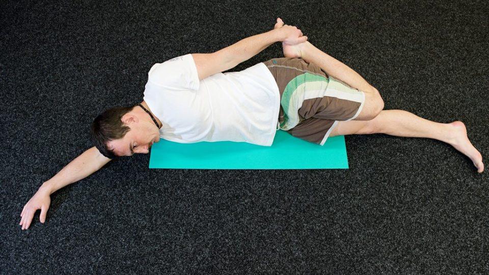 Protažení přední strany stehna vleže na boku. Důležitá je stabilní poloha, se kterou nám pomáhá natažená ruka. Pomocí druhé ruky přitáhněte s výdechem pokrčenou nohu
