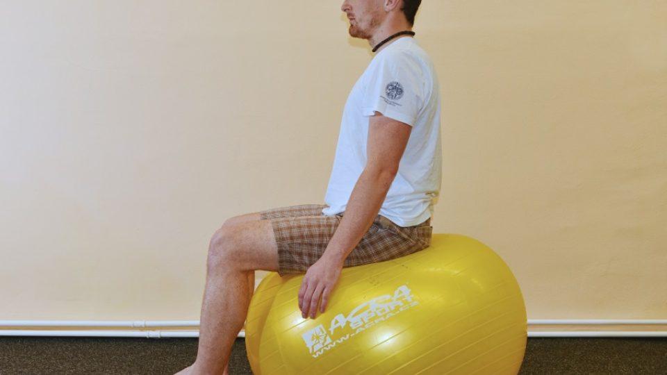 Základní poloha sezení na míči – chodidla celou plochou na zemi, mezi stehny a trupem je pravý úhel. Hlava je rovně, nikoli v předklonu nebo záklonu. Ruce jsou volně položené na míči