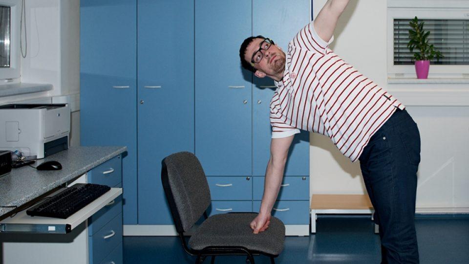 S oporou o židli se s nataženou horní končetinou a společně s hlavou lehce vykruťte v trupu. Podívejte se za horní končetinou a pomalu se vraťte zpět do opory polohy, kdy se opíráte o židli oběma rukama. To samé proveďte na druhou stranu