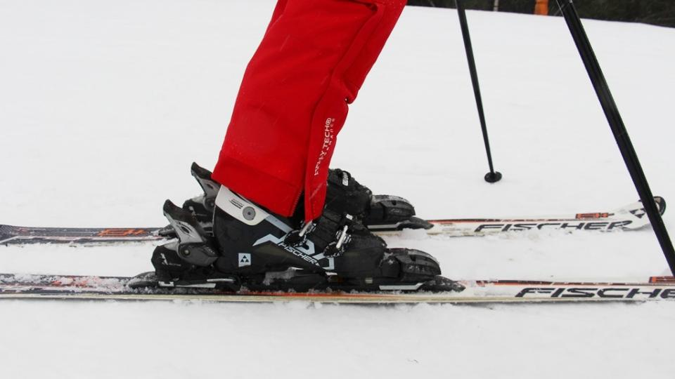 Bota připnutá ve vázání. Lyži s vázáním je důležité před každou zimou svěřit odborníkům, kteří vázání seřídí tak, aby při pádu dokázalo vypnout a předešlo se tak zbytečnému zranění
