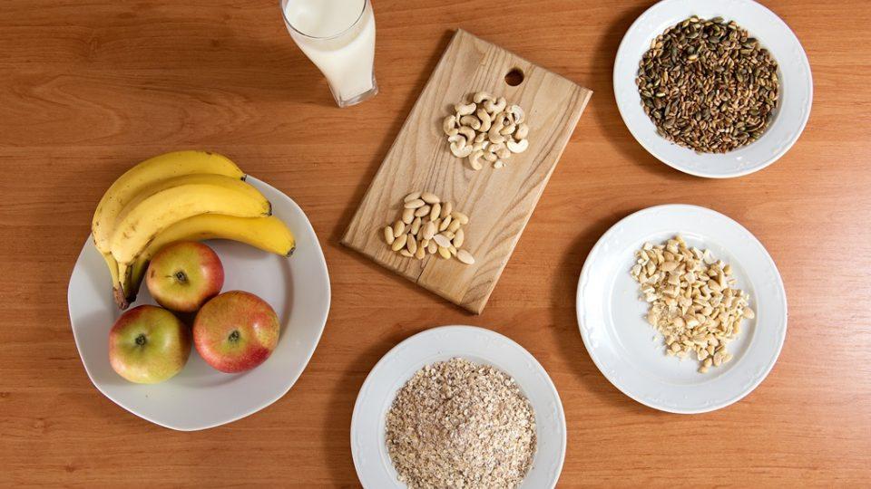 Základní suroviny pro přípravu ovesné kaše: mléko, jemné ovesné vločky, ořechy, opražená semínka a ovoce