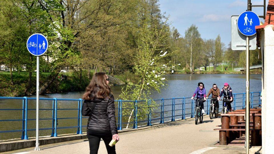 Označení smíšené cyklostezky pro chodce a cyklisty. Značka vlevo upřesňuje, že mají oddělené pruhy