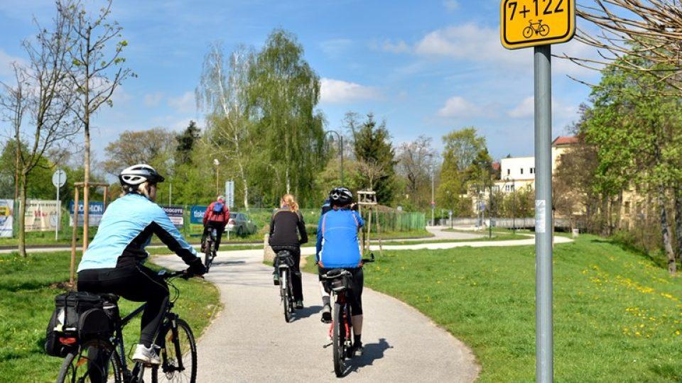 Smíšená cyklostezka pro chodce a cyklisty je označena kulatou modrou dopravní značkou, žluto-černá cedulka pod ní vyznačuje cyklotrasu
