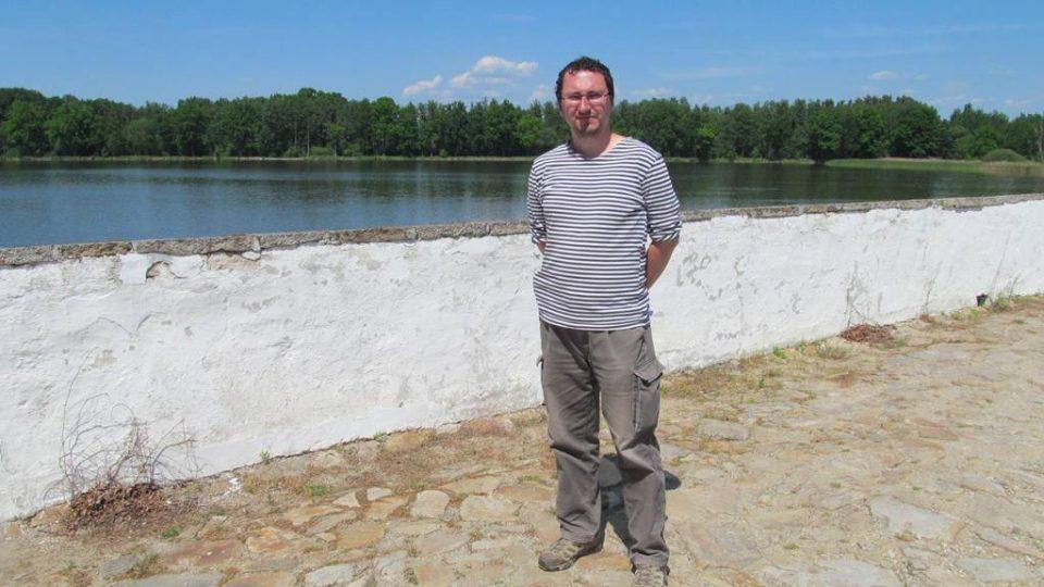 Publicista Jan Ciglbauer na kamenném mostě mezi Starou a Novou Hlínou, z něhož nacisté sypali popel popravených do rybníka Vítek