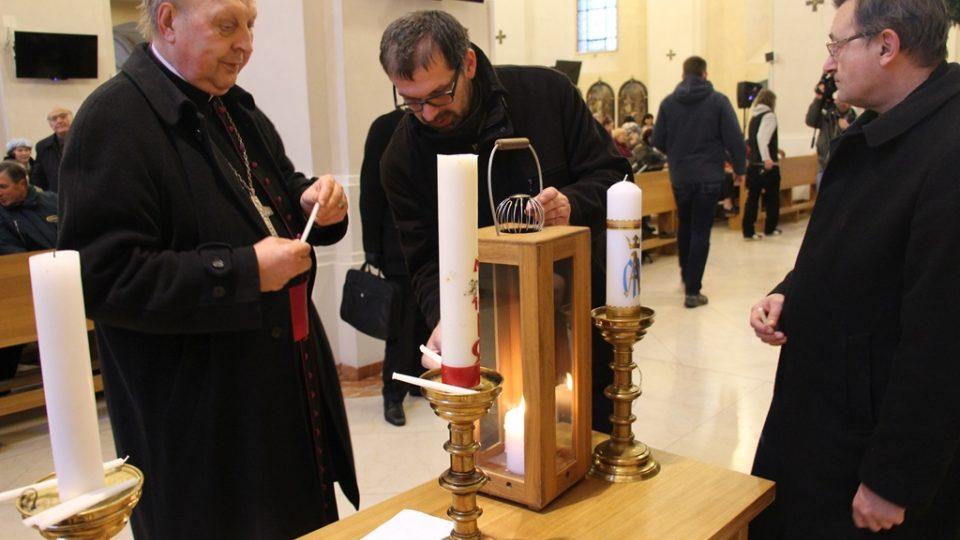 Redaktor Filip Černý předává Betlémské světlo v českobudějovické katedrále
