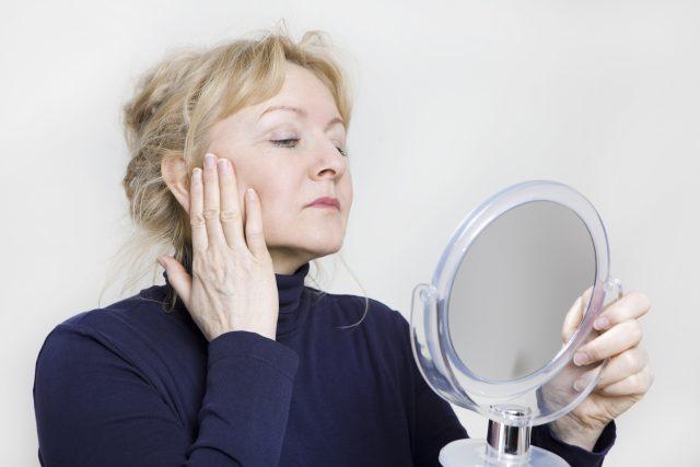 Starší žena se dívá do zrcadla