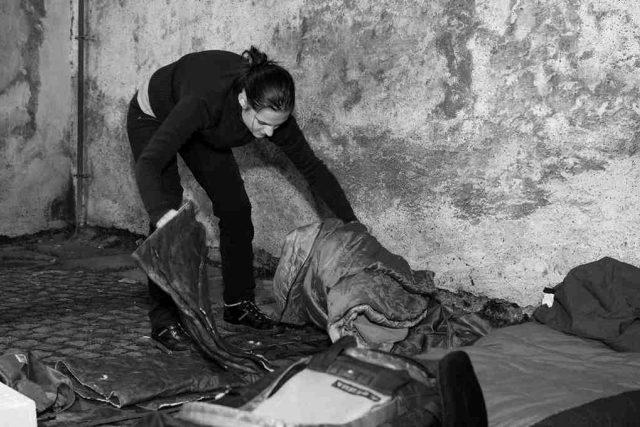 Romana si připravuje místo na spaní na chladných kostkách