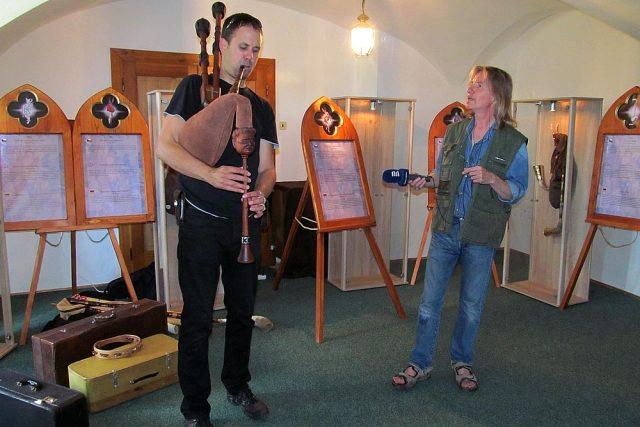 Míla Vaváček hraje na historické dudy pro mikrofon redaktora Zdeňka Zajíčka