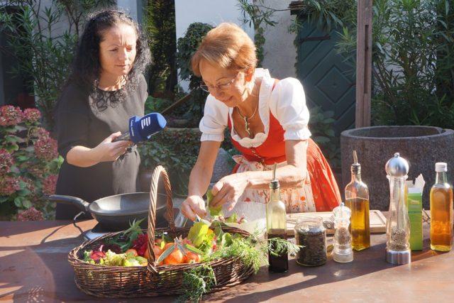 Christine Saahs připravuje na velkém dubovém stole na dvoře své nejoblíbenější jídlo - salát z divokých bylinek a květin