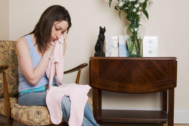 Matka truchlí po ztrátě dítěte, smutek, mateřství, smrt dítěte, dětské oblečení. Ilustrační foto
