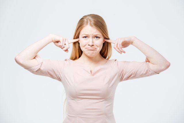 Žena s prsty v uších, neslyší, neposlouchá, zoufalství, neštěstí, ticho, ilustrační foto