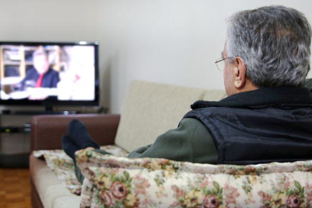 sledování televize, senior kouká na televizi, obývací pokoj, gauč, pohovka, televizní zábava. Ilustrační foto