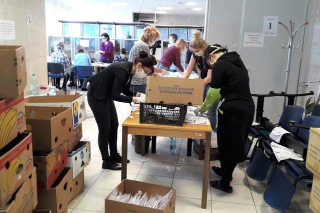 Lidé na městském úřadě v Českém Krumlově kompletují balíčky s rouškami a rukavicemi, které dostane každý obyvatel