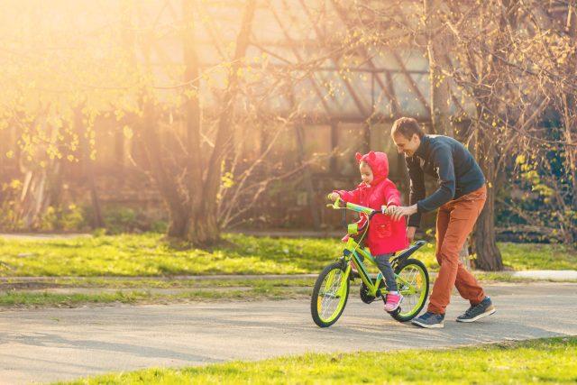 Otec učí dceru jezdit na kole, otec a dcera, rodina, dítě, ilustrační foto