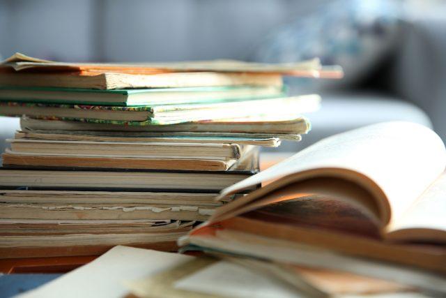 Staré knihy, stoh starých knih na stole (ilustrační foto)