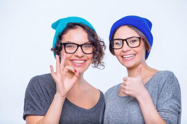 Sestry, kamarádky, podobné ženy, přátelství, úsměvy, čepice, brýle. Ilustrační foto
