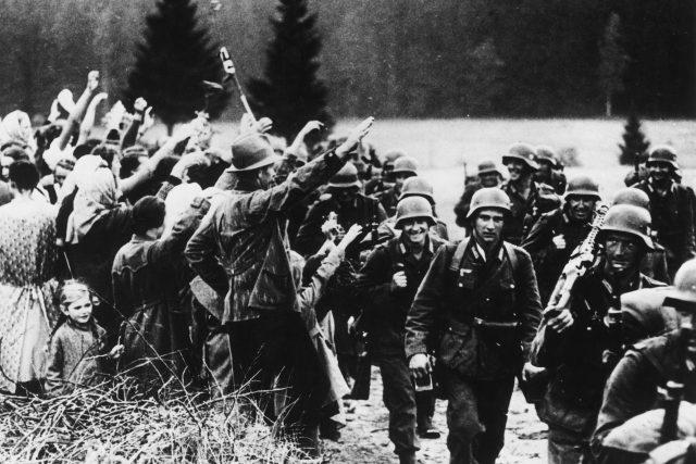 Obsazování Sudet po Mnichovské dohodě 1938. Sudetští Němci zdraví vojáky nacistickým pozdravem